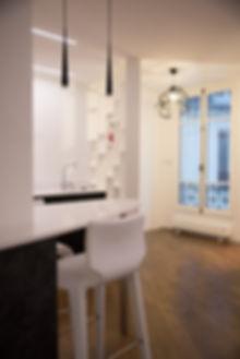 Une cuisine noir et blanche design et mise à distance de l'entrée par un meuble claustra. Rénovation d'un appartement haussmannien de 160m2 à Paris 1er. Meubles noirs, plan de travail corian, coin repas, meuble bibliothèque claustra, parquet chêne. Design Morgane Coroller.