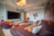 Salon TV haussmannien original et coloré. Rénovation d'un appartement haussmannien de 160m2 à Paris 1er. Papier peint panoramique art Rebel Walls, moblier roche-bobois, bibliothèque médium peint, parquet chêne, moulures. Design Morgane Coroller