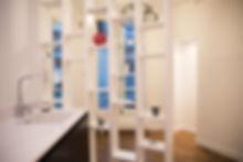 Une cuisine noir et blanche design et mise à distance de l'entrée par un meuble claustra. Rénovation d'un appartement haussmannien de 160m2 à Paris 1er. Meubles noirs, plan de travail corian, meuble bibliothèque claustra, parquet chêne. Design Morgane Coroller.