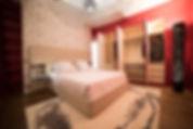 Une chambre rouge et beige. Rénovation d'un appartement haussmannien de 160m2 à Paris 1er. Tête de lit papier-peint, cuir, tapis, lit king size, dressing sur mesure bouleau, suspension vertigo, parquet chêne. Design Morgane Coroller