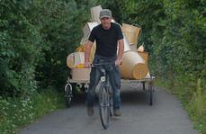 Der Künstler - Roger Aupperle - auf einem Fahrrad mit Anhänger auf dem 48 Lampenschirme installiert sind.