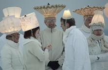 Sieben ganz in weiß gekleidete Personen mit leuchtenden Lampenschirmen auf dem Kopf.
