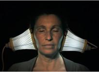 Frau mit Lichthörern auf den Ohren versucht mit geschlossenen Augen Licht zu hören.