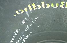 Close-up eines ehemaligen Mülleimers in dessen Wandungen ein Schriftzug eingelassen ist. Haiku eines japanischen Dichters.