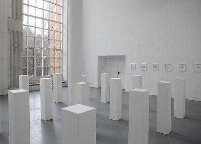 16 weiße Sockel sind in gleichmäßigen Abständen zu einem großen Quadrat installiert und stehen in einem ansonsten leeren weißen Raum.