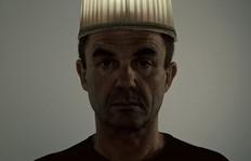 Der Künstler - Roger Aupperle - ist mit einem leuchtendem Lampenschirm auf dem Kopf zu sehen.