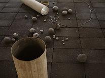 Installation mit Fundstücken und elektrischem Licht auf komprimierter Kohle.