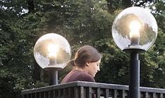 Mädchen sitzt im Park zwischen zwei Laternen und versucht mit geschlossenen Augen Licht zu hören