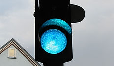 Close-up einer Ampel, mit blauen anstatt grünem Licht im untersten Fenster.