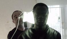 ein dunkelhäutiger Man mit grell leuchtenden Lichthören auf den Ohren versucht mit geschlossenen Augen Licht zu hören. Der Künstler - Roger Aupperle - steht im Hintergrund.