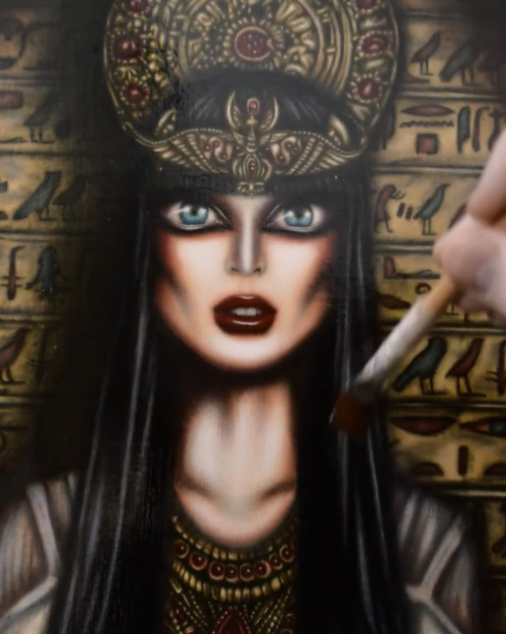 painting of cleopatra with blue eyes a crown and hieroglyphs behind her by tiago azevedo a lowbrow pop surrealism artist