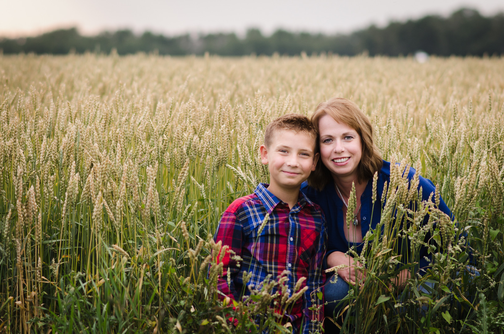 mom and son sitting in wheat field smiling