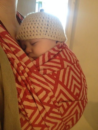 A sleeping newborn is on her mother in a red and cream wrap, wearing a crochet hat.