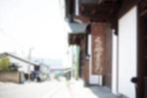切妻破風のひさし(写真奥)と招き屋根の庵看板・くめや重右衛門