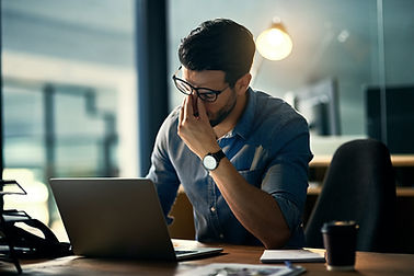 Stressed Man at a desk on a laptop pinching his nose in frustration. He could benefit from an online therapist specializing in counseling for men. Marble Wellness has online therapy in Illinois with focus in online therapy in STL and online therapy in Chicago, IL.