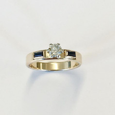 Half carat diamond solitaire ring with two black sappires on shoulders. Claw set.