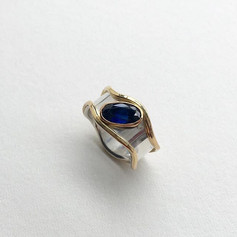 Large sapphire set into a silver wave band ring with 9ct bezel and edges.