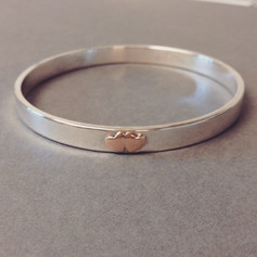 Silver bangle with two hearts