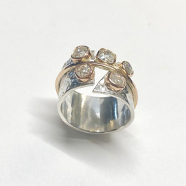 Large diamonds set into reticulated silver ring with gold bezels