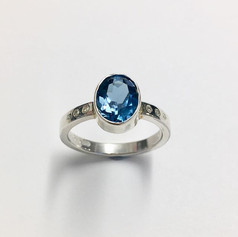 Silver and large topaz ring with diamonds on shoulders.