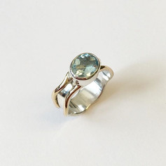 Large topaz set into sterling silver wave band with 9ct gold edges.