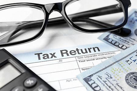 bigstock-Tax-return-form-glasses-calc-18