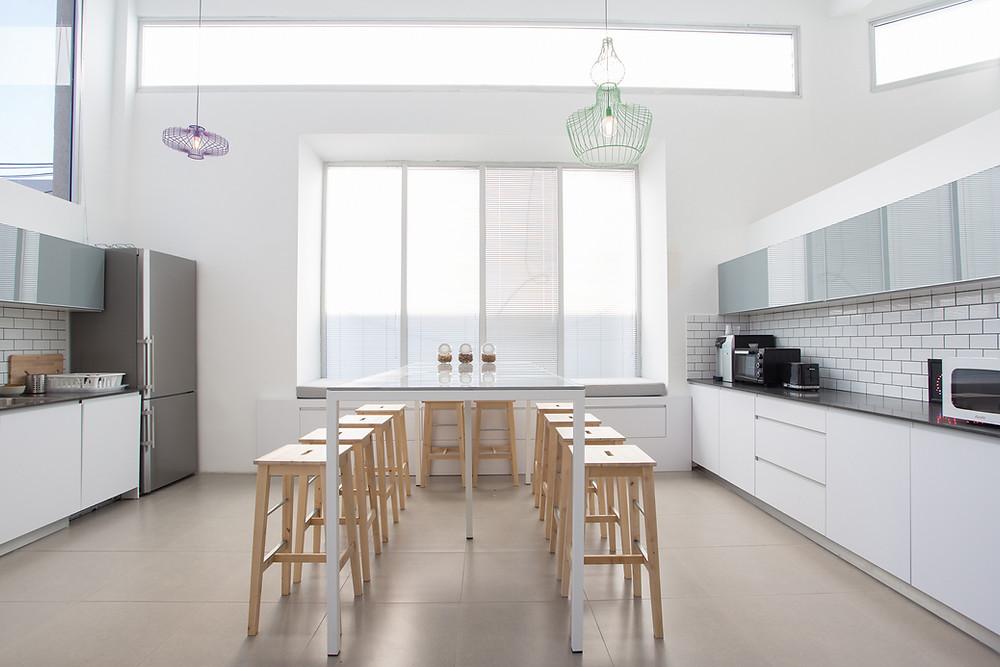 Die Abstände zwischen den Küchenzeilen sind groß und der Esstisch steht als funktionelle Barriere dazwischen