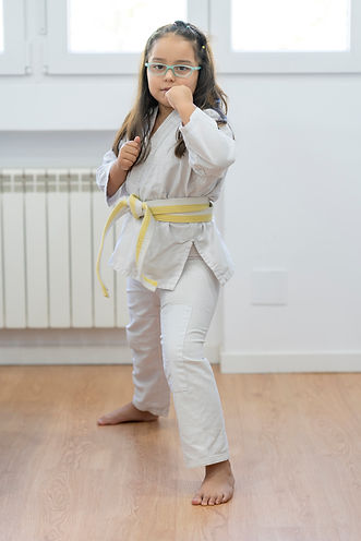 Girl with karate kimono and white and ye