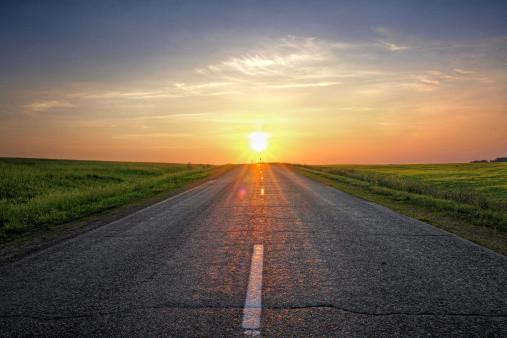 a road leading towards a sunrise