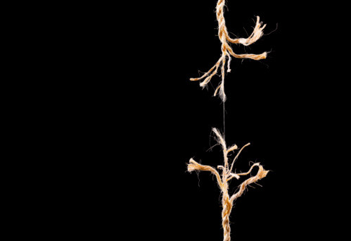 a fraying rope, nearly split and hanging by a thread