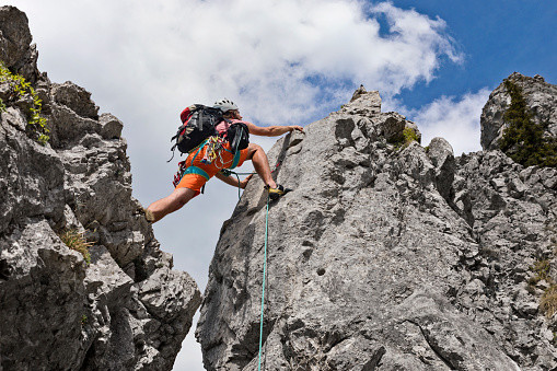 a person with a backpack climbs from one rock to another