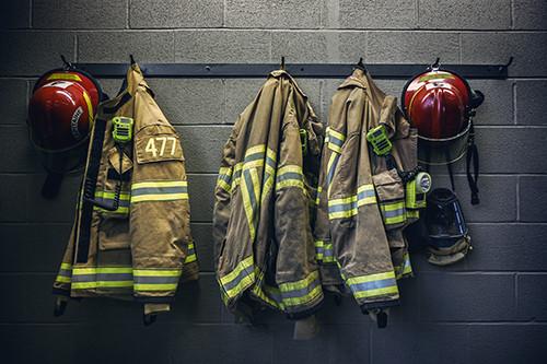firefighter coats and helmets hang along a wall