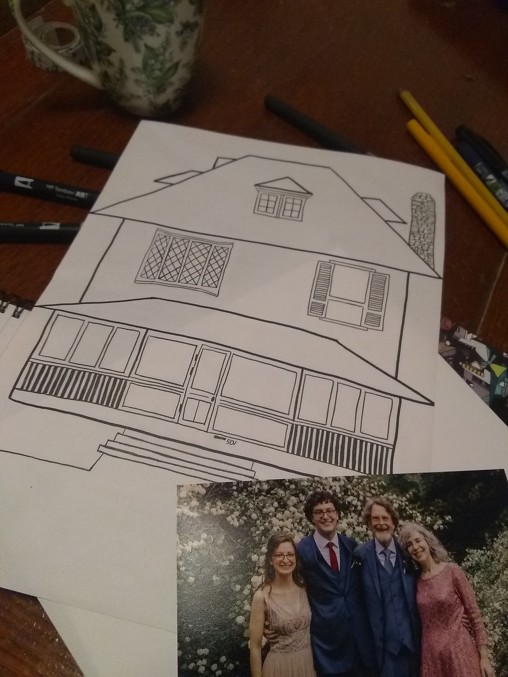 A drawing of my house and a photo of my family.