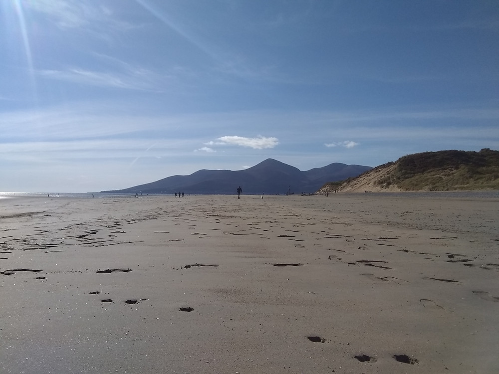 a beach full of footprints and hills in the distance