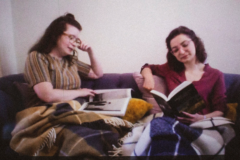 Melissa McGuigan. Facetime photoshoot. Two girls reading books on the sofa.