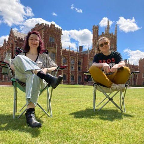 Two girls sit in camping chairs in front the Lanyon building, Queen's University Belfast.