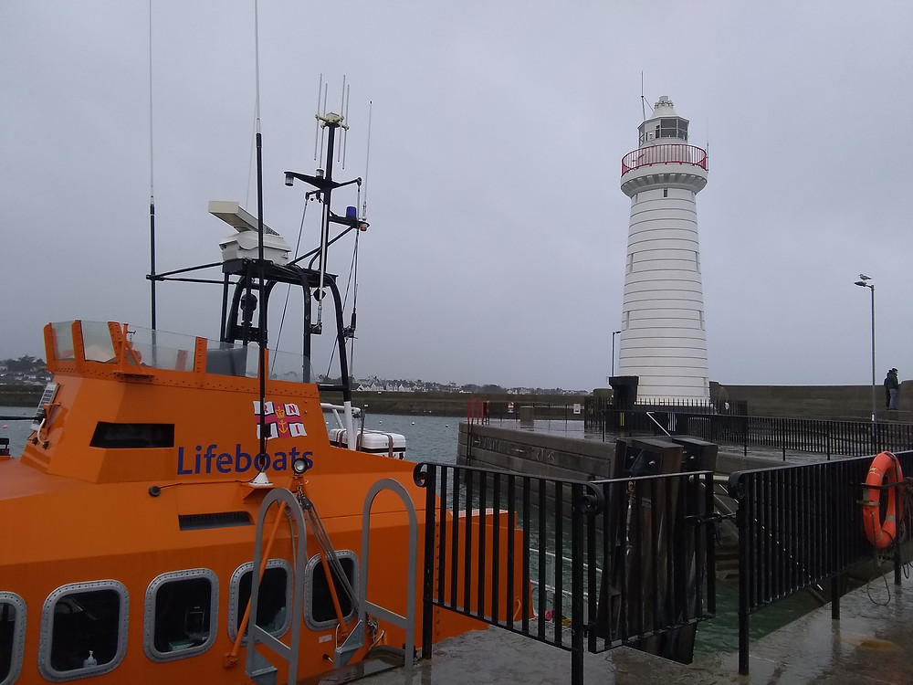 A bright orange lifeboat and a white lighthouse