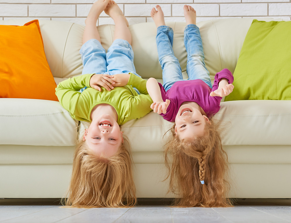 Two girls playing on sofa