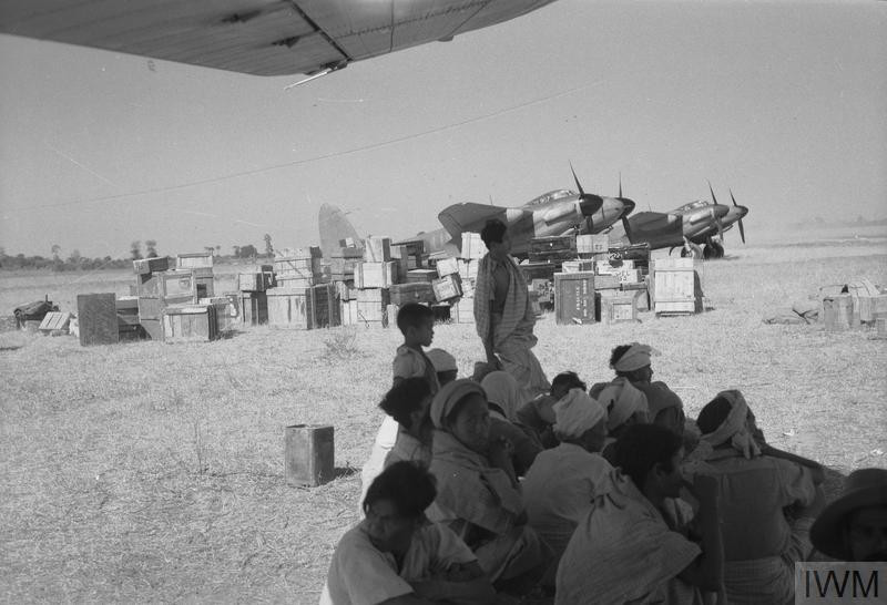 THE WAR IN THE FAR EAST: THE BURMA CAMPAIGN 1941-1945 (CF 324) Air Force Operations: Burmese bearers on a Royal Air Force airstrip in Burma sheltering from the midday sun under the wing of a Dakota. In the background are boxes of supplies brought by air and two De Havilland Mosquito photo reconnaissance aircraft belonging to No 684 Squadron, Royal Air Force. Copyright: © IWM. Original Source: http://www.iwm.org.uk/collections/item/object/205194203