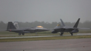 Two United States Air Force F-22 aircraft arrive at RAAF Base Tindal under grey skies and rain in the Northern Territory, ahead of the first Enhanced Air Cooperation activity in Australia.