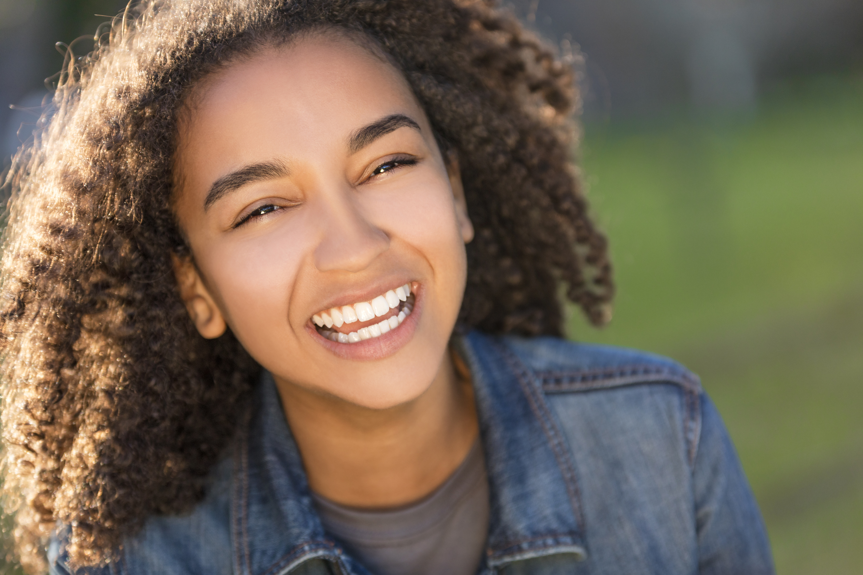Outdoor portrait of beautiful happy mixed race African American girl teenager female young woman smi