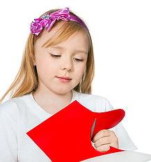 beautiful blonde girl cuts red cardboard