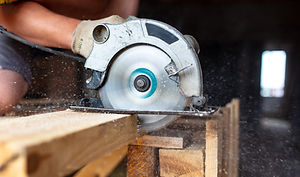 A worker saws a wooden beam. Building a