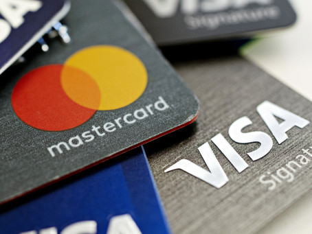 Visa, Mastercard to delay merchant fee hikes another year.