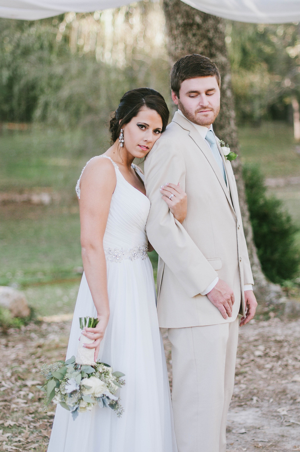 Wedding in the woods in Tennessee. Bride is leaning against groom for wedding pose. Bride is holding bouquet upside down. Jonesboro, AR Photographers. Jonesboro, AR photographer