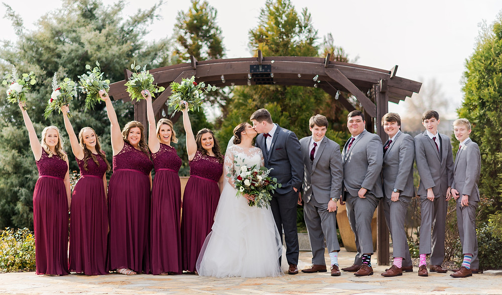 Wedding at Harmony Gardens in Jonesboro, Arkansas. Bridesmaids are in maroon dresses and holding their bouquets from Southern Style Florist in the air. Groomsmen are showing off their silly socks that they chose to wear on the wedding day. Bride and groom are kissing. Jonesboro, AR Photographers. Jonesboro, AR photographer