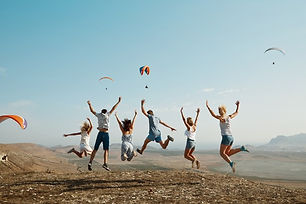 group-of-friends-jumping-on-top-of-hill_