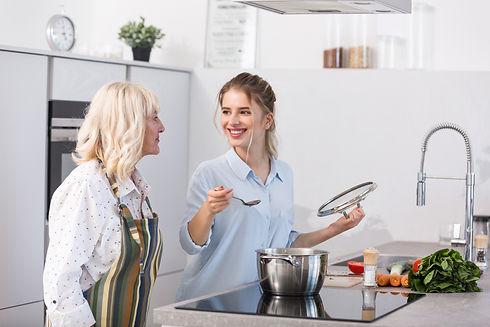 happy-granddaughter-her-grandmother-cook