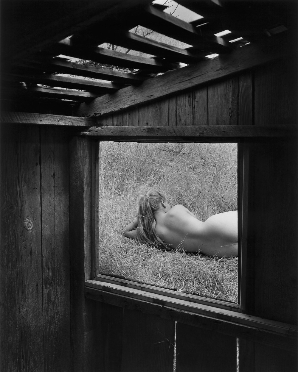 Photo : Barbara through Window, Wynn Bullock, Wynn Bullock Family Photography Estate - Courtesy Laurence Miller Gallery. Photo en noir et blanc d'une femme nue allongée dans l'herbe, vue à travers la fenêtre d'une cabane en bois.