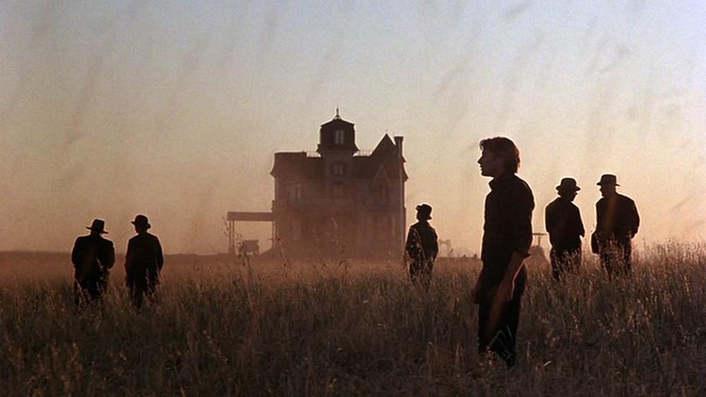 Photo du film Les Moissons du ciel, Terrence Malick, Richard Gere. Des hommes dans un champ de blé, une maison isolée en arrière-plan.